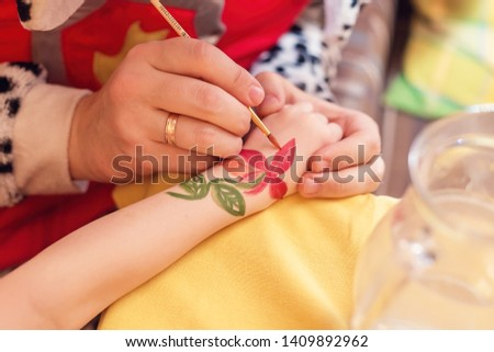 The animator on the hand of the child paints a red flower