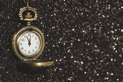 The antique clock shows almost midnight against a sparkling black background. New year concept. Place for your text.