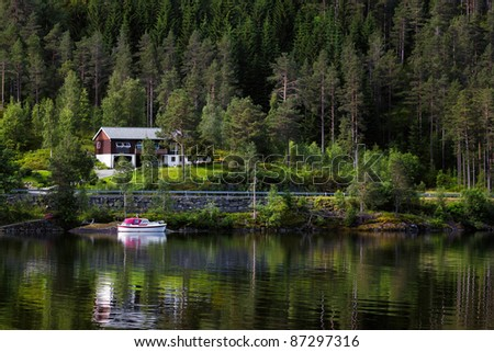 The apartment house standing on the bank of fjord, against dense coniferous wood with a boat at coast, Norway.