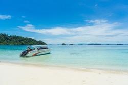 The aqua sea and white sand beach with speedboat
