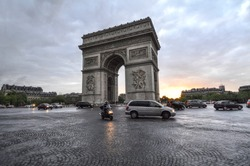 The Arc De Triomphe monument stands against sunset skies in Paris, France. Cars travel through the cobblestone roundabout at Place Charles De Gaulle, circling the historic French landmark.