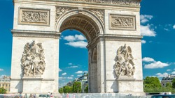 The Arc de Triomphe (Triumphal Arch of the Star) timelapse is one of the most famous monuments in Paris, standing at the western end of the Champs-Elyseees. Traffic on circle road. Blue cloudy sky at