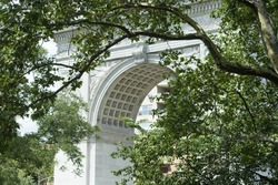 The arch framed by tree branches at Washington Square Park in Greenwich Village New York City.
