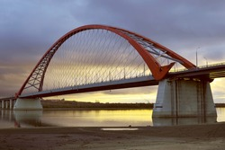 The arch of the Bugrinsky highway bridge across the Ob River in Novosibirsk. Yellow-blue sky at dawn. Sandy beach. Golden Horizon. Bright