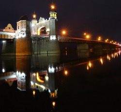 The arch of the Queen Louise Bridge across the Neman in the city of Sovetsk is reflected in the water at night. Panorama