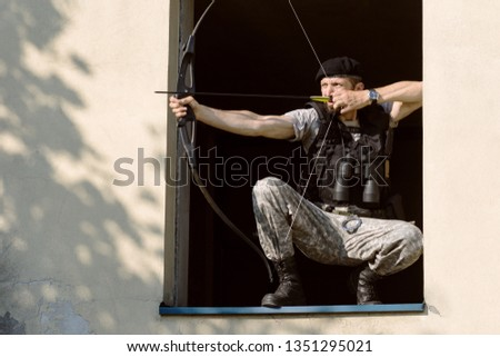 The archer is aiming with bow and arrow in the window, archery concept. #1351295021
