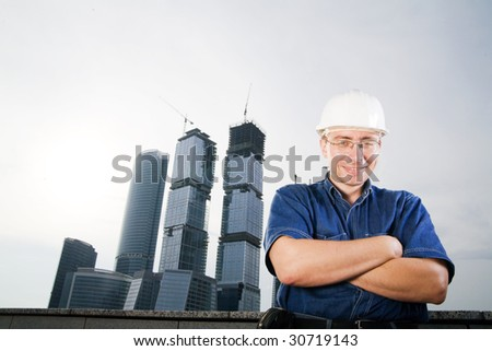 The architect wearing a protective helmet standing in front of a building site - stock photo