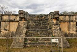 The architecture of the ancient Mayan city of Chichen Itza. Steps lead to the top of the stone platform. On the side are the heads of a serpent carved from stone. The sky is cloudy. Mexico