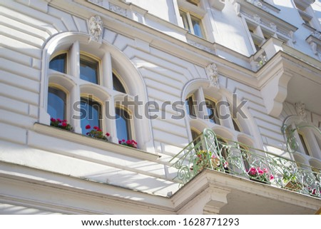The architecture of the Old Town part of the Prague. Details and elements of architectural decorations on the facades of houses. Windows with flowers close up.
