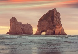 The Archway Islands of Wharariki Beach at sunset in New Zealand