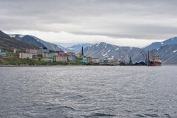 The Arctic port town of Provideniya. View of the sea bay, settlement and mountains. Provideniya port is part of the Northern Sea Route. Provideniya, Providence Bay, Chukotka, Far East of Russia.