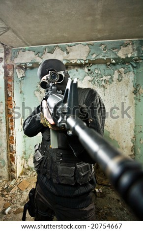 The armed soldier in a camouflage costs in alertness on a gray background