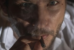 The art photography of the male face is covered with cigarette smoke. The adult man smokes the cigar. Man looking at the cigarette butt through the smoke.