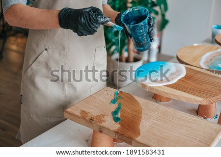 The art process of pouring epoxy resin into a wooden tray Сток-фото ©