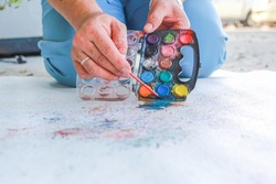 The art teacher is using the hand to hold the brush To paint the watercolor With many colors Onto the floor of white paper And there is a tray of small watercolor near Used as an illustration