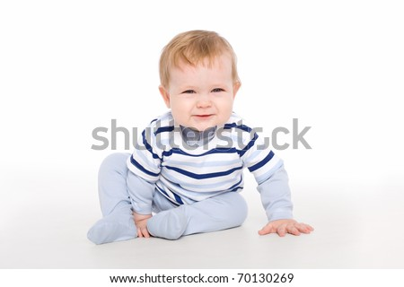 The artful toddler boy sitting on the floor