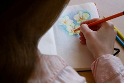 The artist draws flowers with pencils on paper. Art Studio. Drawing flowers. Ideas of creativity.