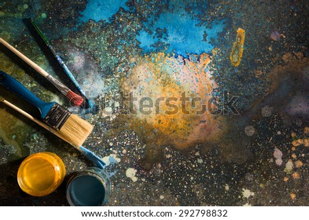 The artist\'s palette. Spray droplets and smears on a dark background. Nearby are open cans of paint and brushes.