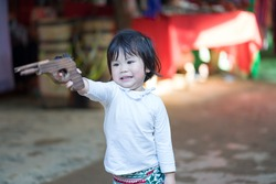 The asian baby girl playing a wood gun.She very happy and fun.