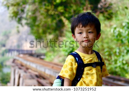 The asian boy (Taiwanese) visits the famous Death railway which is nearby the cliff and Kwai River in Tham Krasae, Kanchanaburi, Thailand. #1073251952