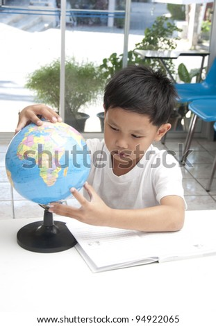 The Asian boy with globe model in the library