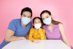 The asian family is wearing a mask to protect against viruses on pink background.