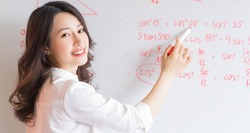 The Asian female teacher is rewriting the lecture on the board