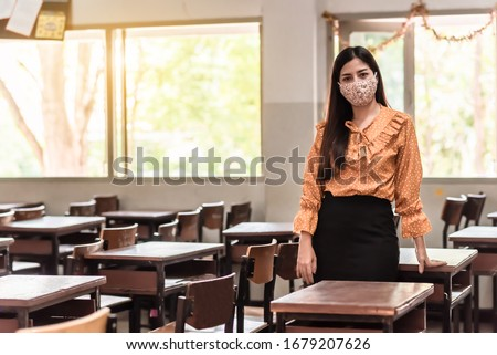The Asian female teacher is wearing a mask and standing in the empty classroom because of living at risk in the midst of Coronavirus disease 2019 (COVID-19) epidemic.