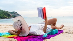 The Asian girl reads alone at the beach, lonely, wearing a white hat, wearing a ukulele over her in the summer relaxing in the tropical sea.
