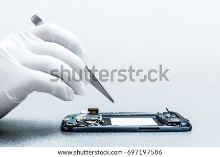 The asian technician repairing the smartphone's motherboard in the lab with copy space. the concept of computer hardware, mobile phone, electronic, repairing, upgrade and technology.