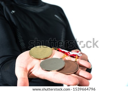 The athlete holds various medals in his hands, isolated trophies. Gold, silver and bronze medal in hands. The concept of tournaments and competitions. Victory, winning competitions. #1539664796