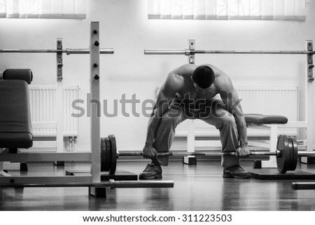The athlete in the gym. Professional weightlifting. Weight training. Work on tell muscles. The success achieved by effort.