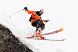 The athlete skier on a light background with a jump moves off the roof of a snow-covered hut with flying flakes of snow. The concept of winter ski sports