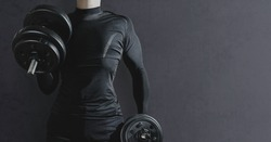 The athlete trains dumbbells on a dark background. Sport concept and taking care of the figure. The man lifts dumbbells, cares for his muscles. Weightlifting, sports training.