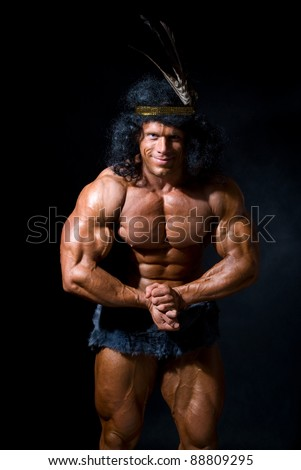 The athletic man with a feather on a head on a black background