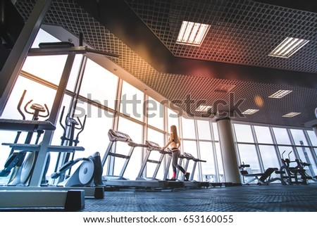 The athletic woman running on the treadmill in the gym