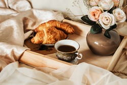 The atmosphere of a romantic morning, coffee in bed. Flowers in a vase, french croissants and a cup of coffee on a wooden tray on a silk bed. Home interior. Lifestyle