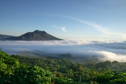 The atmosphere of Mount Batur in the morning where the caldera is covered by low stratus clouds. The sky looks bright blue and green vegetation around Mount Batur