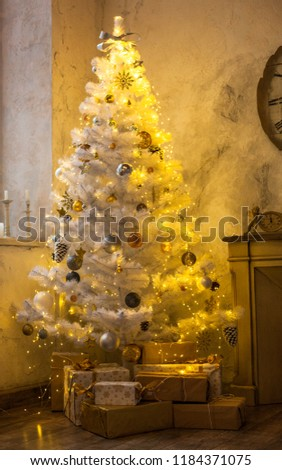 The atmosphere of the holiday. New Year's interior. Wall clock with fireplace and Christmas tree #1184371075