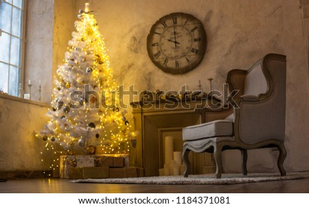 The atmosphere of the holiday. New Year's interior. Wall clock with fireplace and Christmas tree #1184371081