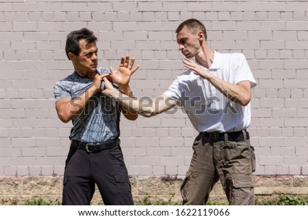 The attacker grabs the opponent by the clothes. Acceptance of exemption from capture. Martial arts instructors demonstrate self-defense techniques of Krav Maga