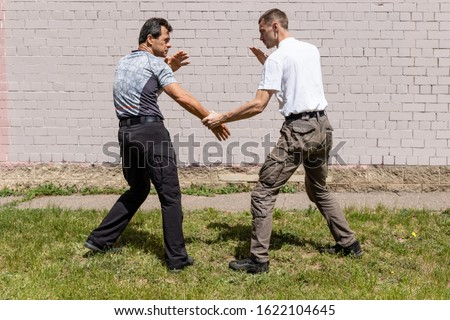 The attacker is trying to hold the man by the wrist. Opponents are ready for a fight. Martial arts instructors demonstrate self-defense techniques of Krav Maga