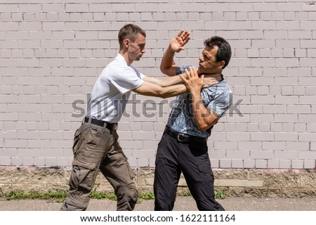 The attacker is trying to strangle the man. The defender begins to perform a special technique against strangulation. Martial arts instructors demonstrate self-defense techniques of Krav Maga