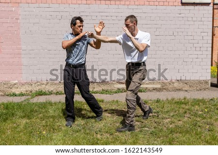 The attacker is trying to strike a fist in the face. The defender goes away from the attack. Martial arts instructors demonstrate self-defense techniques of Krav Maga