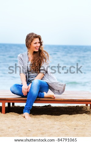 The attractive bright girl sits on the bank of a beach smiles - stock photo