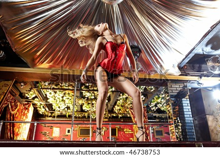The attractive girl dances a striptease in club