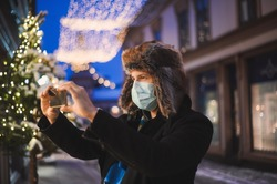 the attractive kind man in a fur hat and face mask with illuminated city lights  at night during the celebration of Christmas and on New Year's Eve 2021 during the coronavirus covid-19 pandemic