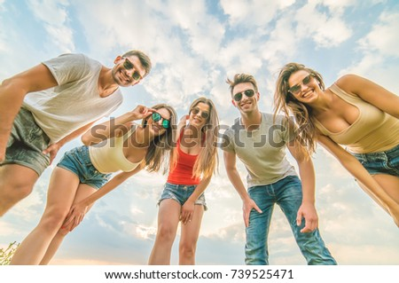 The attractive people look to the camera on the background of clouds #739525471