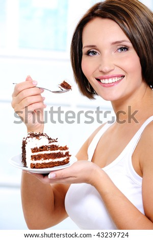 The attractive smiling young girl with a sweet cake slice on a plate brings a spoon to a mouth