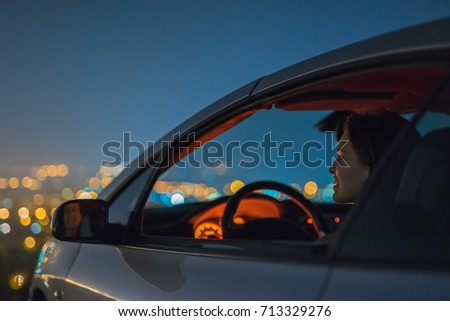 The attractive woman sit in the car on the background of the city. night time  #713329276